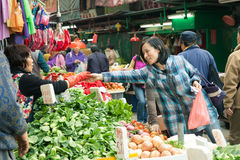Woman buying vegetables in the street market, Hong Kong. HONG KONG - FEB 17, 2014: Woman buying vegetables in the street market, Hong Kong, February 17, 2014 royalty free stock photography