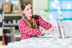 Woman buying wallpapers in do.it-yourself store Royalty Free Stock Image