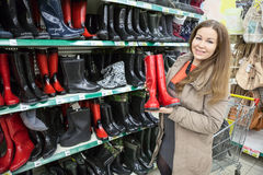 Woman buying waterproof shoes in shopping center. Woman buying waterproof shoes in the shopping center royalty free stock photos