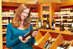 Woman buying wine in supermarket Stock Images