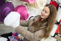 Woman buying winter hat in shopping center Stock Photo