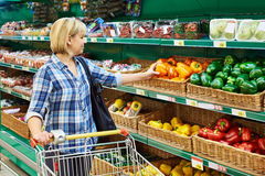 Woman buys bell peppers in store Stock Photos