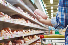 Woman buys boiled sausage in supermarket Royalty Free Stock Images