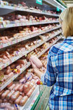 Woman buys boiled sausage in supermarket Stock Photo