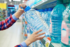 Woman buys bottle drinking water in shop Royalty Free Stock Photos