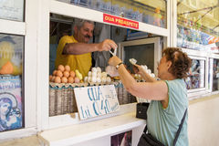 Woman buys eggs at the marketplace Royalty Free Stock Photos