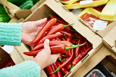 Woman buys hot red peppers in store Stock Photo