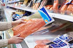 Woman buys lightly salted red fish in store Royalty Free Stock Photo