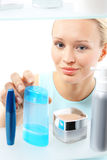 Woman buys liquid make-up remover. Royalty Free Stock Photo