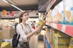 Woman buys quick breakfasts at a supermarket. Girl isa in the store with a box of flakes and hands stock images