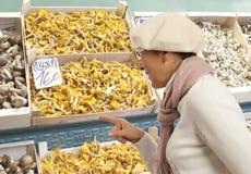 Woman buys raw mushroom in market Stock Photo