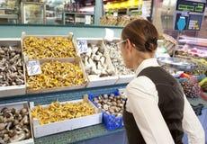Woman buys raw mushroom in market Royalty Free Stock Image