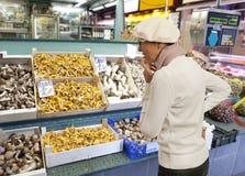 Woman buys raw mushroom in market Stock Image