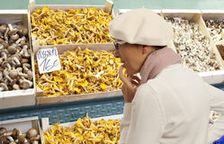 Woman buys raw mushroom in market Royalty Free Stock Photography