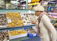 Woman buys raw mushroom in market Stock Images