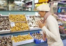 Woman buys raw mushroom in market Royalty Free Stock Photos