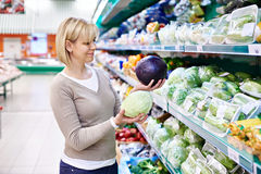 Woman buys a red and white cabbage in store Royalty Free Stock Photo
