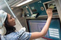 Woman buys a ticket vending machine Stock Photo