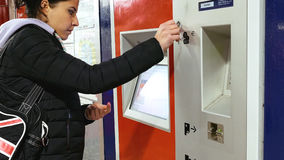 Woman buys tickets at subway station. Hamburg, Germany - October, 10, 2016: Ticket machine in metro subway underground tube is being used by young lady. Woman Royalty Free Stock Images