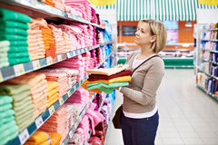 Woman buys towels in supermarket Stock Image