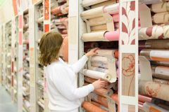 Woman buys wallpaper in  store Stock Photo