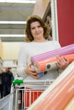 Woman buys wallpaper in  store Royalty Free Stock Images