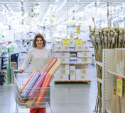 Woman buys wallpaper in  store Stock Images