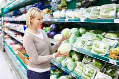 Woman buys white cabbage in store Royalty Free Stock Photos