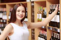 Woman buys wine in a store. Light citrus wine. Close-up of a young smiling woman taking a wine bottle from the store shelf and smiling to the camera satisfied stock photography
