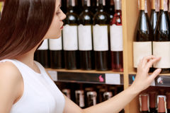 Woman buys wine in a store Royalty Free Stock Image