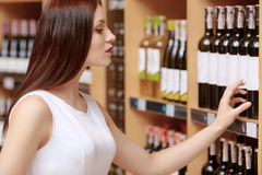 Woman buys wine in a store Stock Image
