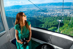Woman in cable car with cityscape view Stock Images