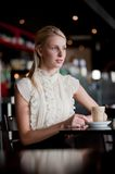 Woman In Cafe. A young attractive woman sitting in a cafe with a coffee royalty free stock images
