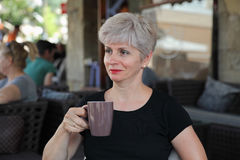 Woman in cafe drinking coffee Stock Image