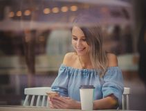 Woman in a cafe and drinking coffee and use mobile phone while sitting by the window stock photos