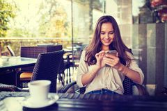 Woman in cafe drinking coffee and using her mobile phone. Young woman in cafe drinking coffee and print the message on mobile phone. Smiling girl with smart Stock Image