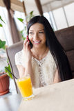 Woman in cafe drinking orange juice, smiling talking on mobile Stock Photos