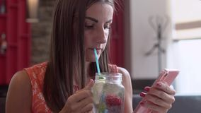 A woman in a cafe, drinks a smoothie, leafs through the menu, reads messages on the phone and writes the answer. Close stock footage