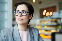 Woman in cafe. Female in eyeglasses having rest in cafe Royalty Free Stock Image