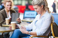 Woman at a cafe looking at her smart phone Stock Image