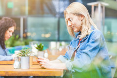 Woman at a cafe looking at her smart phone Stock Photos