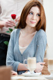 Woman at the cafe and man with rose behind her Royalty Free Stock Images