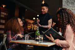 Woman in a cafe ordering to waiter. Young women with a friend ordering to waiter holding digital tablet. Two women sitting at cafe holding menu card giving an Stock Image