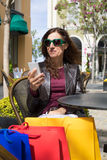 Woman in cafe oudoors with shopping bags watching mobile Stock Images