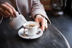 woman in a cafe pours milk cream into coffee cup Stock Images