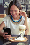 Woman in cafe with smartphone Royalty Free Stock Image
