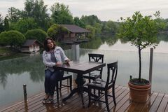 Woman at a cafe table by the pond. People Royalty Free Stock Photography