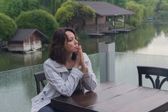 Woman at a cafe table by the pond. People Royalty Free Stock Photo