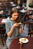Woman In Cafe Taking Food Photo On Mobile Phone. Attractive Girl Making Photos In House. High Resolution royalty free stock photos