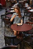 Woman In Cafe Taking Food Photo On Mobile Phone. Attractive Girl Making Photos In House. High Resolution stock images